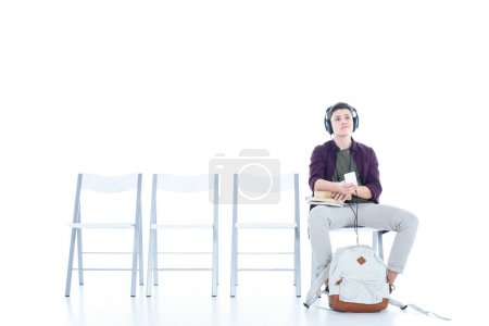 bored teenage student boy listening music while sitting on chair isolated on white