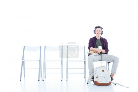 smiling teenage student boy listening music while sitting on chair isolated on white