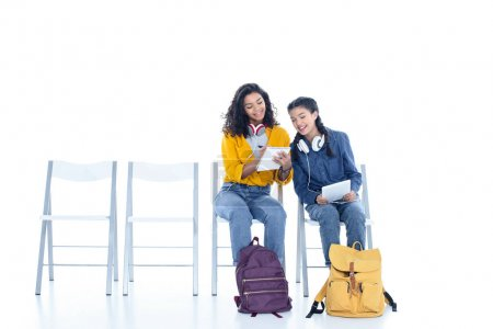 teenage student girls studying together while sitting on chairs isolated on white