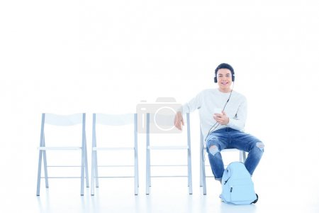 happy teenage student boy listening music while sitting on chair isolated on white