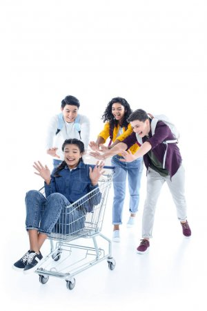 group of teen students riding their friend on shopping cart isolated on white
