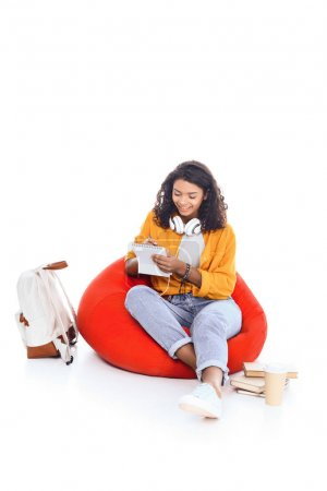 happy teenage african american student girl with headphones studying on bean bag isolated on white