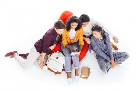 high angle view of group of teen students studying while sitting on bean bag isolated on white