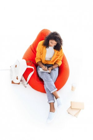 high angle view of teenage african american student girl studying while sitting on bean bag isolated on white
