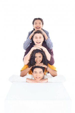 group of teen students lying on each other and looking at camera isolated on white