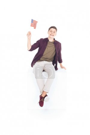 teenage student boy sitting on white cube and looking at camera with usa flag isolated on white
