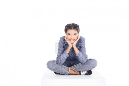 teenage student girl sitting on floor and looking at camera isolated on white