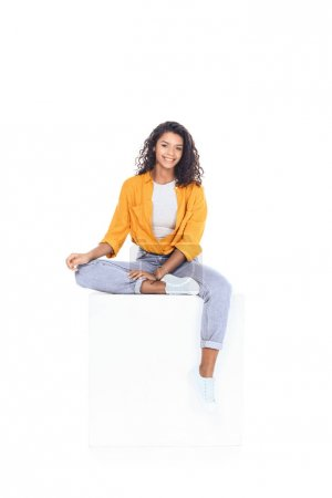 Photo for Teenage african american student girl sitting on white cube and looking at camera isolated on white - Royalty Free Image