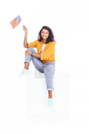 teenage african american student girl sitting on white cube and looking at camera with usa flag isolated on white