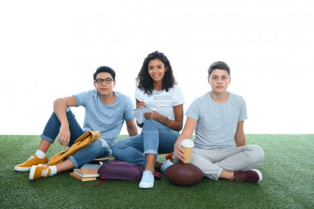 group of multiethnic students studying while sitting on grass isolated on white