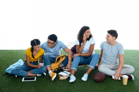group of students studying while sitting on grass isolated on white
