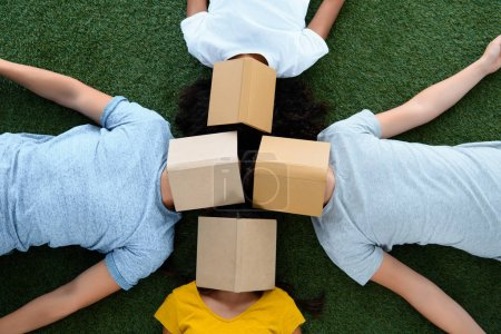 top view of group of students lying on green grass with books on faces