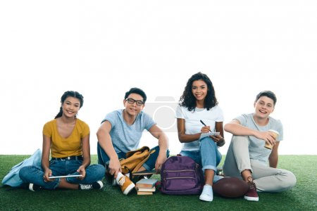 Photo for Group of teen students studying while sitting on grass isolated on white - Royalty Free Image