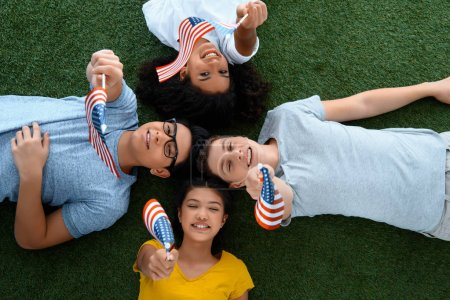 top view of group of teen students with usa flags on green grass