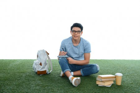 teen asian student boy studying while sitting on grass isolated on white