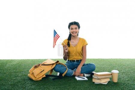 Photo pour Fille adolescente étudiant avec drapeau usa assis sur l'herbe isolé sur blanc - image libre de droit