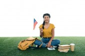 teenage student girl with usa flag sitting on grass isolated on white
