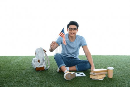 teen asian student boy with usa flag sitting on grass isolated on white