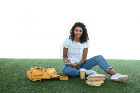 teenage african american student girl studying while sitting on grass isolated on white