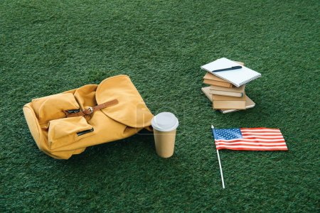vintage yellow backpack and school supplies with usa flag on green grass
