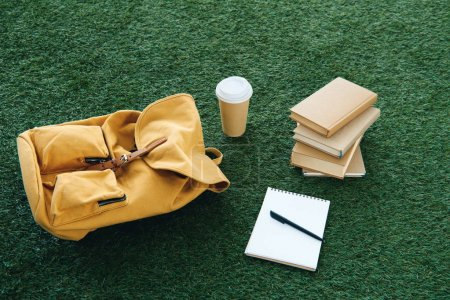 backpack and school supplies on green grass