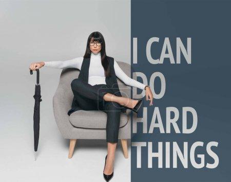 hermosa morena empresaria sentada en sillón con paraguas en gris con usted puede hacer cosas duras