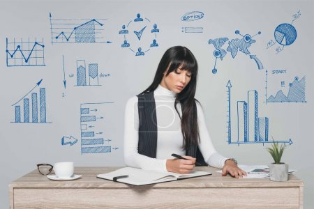 attractive brunette businesswoman writing something at table isolated on gray with hand-drawn business graphs around