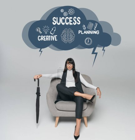 beautiful brunette businesswoman sitting on armchair with umbrella on gray, cloud with creative, success and planning inscription above