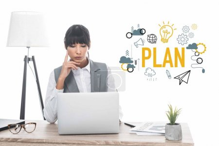 businesswoman sitting at table and looking at laptop isolated on white, plan inscription and business icons