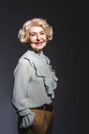 happy senior woman in stylish shirt looking at camera on dark grey
