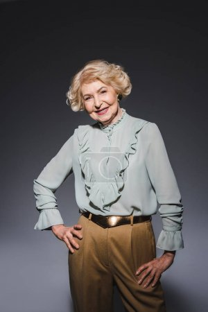 smiling senior woman in stylish shirt looking at camera on dark grey