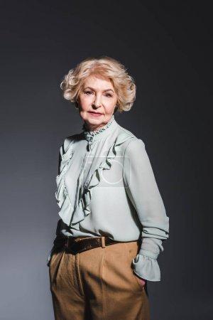 beautiful senior woman in stylish shirt looking at camera on dark grey