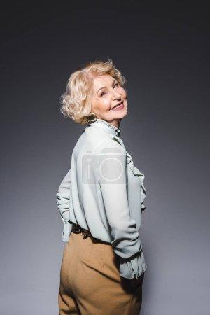 beautiful senior woman in stylish clothes on dark grey