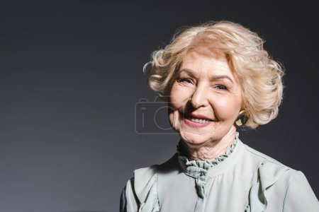 close-up portrait of beautiful senior woman looking at camera on dark grey