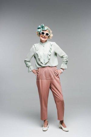 attractive senior woman in stylish headband and sunglasses on grey