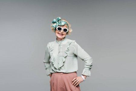 Photo pour Séduisante femme âgée en bandeau élégant et lunettes de soleil isolées sur gris - image libre de droit