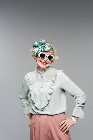 happy senior woman in stylish headband and sunglasses isolated on grey