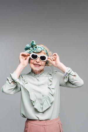 smiling senior woman in stylish headband and sunglasses isolated on grey