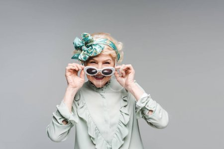 beautiful senior woman in stylish vintage clothes and sunglasses isolated on grey