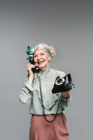 happy senior woman talking by rotary phone isolated on grey