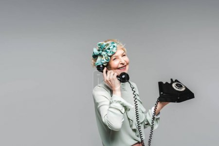 stylish senior woman talking by rotary phone isolated on grey
