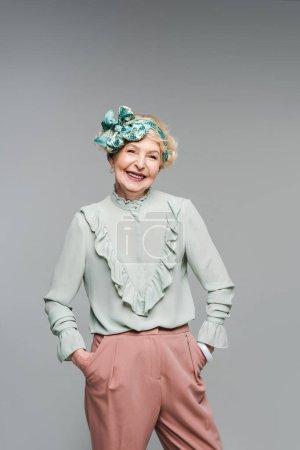 Photo pour Femme senior souriante dans des vêtements élégants, regardant la caméra isolée sur fond gris - image libre de droit