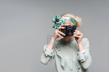 Photo for Stylish senior woman taking photo with vintage film camera isolated on grey - Royalty Free Image