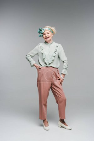 smiling senior woman in stylish vintage clothes on grey