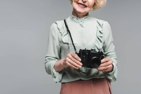 cropped shot of senior woman with vintage film camera isolated on grey