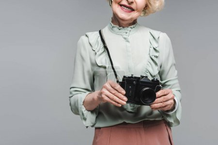 Photo for Cropped shot of senior woman with vintage film camera isolated on grey - Royalty Free Image
