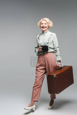 Photo for Stylish senior woman walking with vintage suitcase and film camera on grey - Royalty Free Image