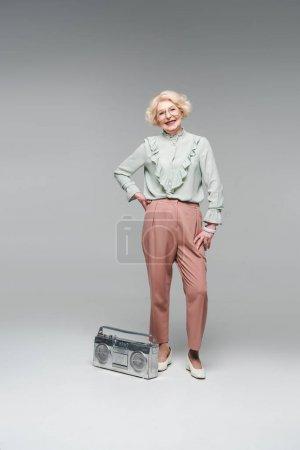 stylish senior woman with vintage boombox isolated on grey