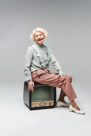 beautiful senior woman sitting on vintage tv on grey