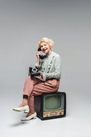 Photo pour Belle femme âgée parlant par téléphone rotatif tout en étant assis sur la télévision vintage sur gris - image libre de droit